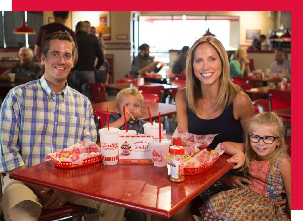 Happy family eating at a Freddy's Franchise
